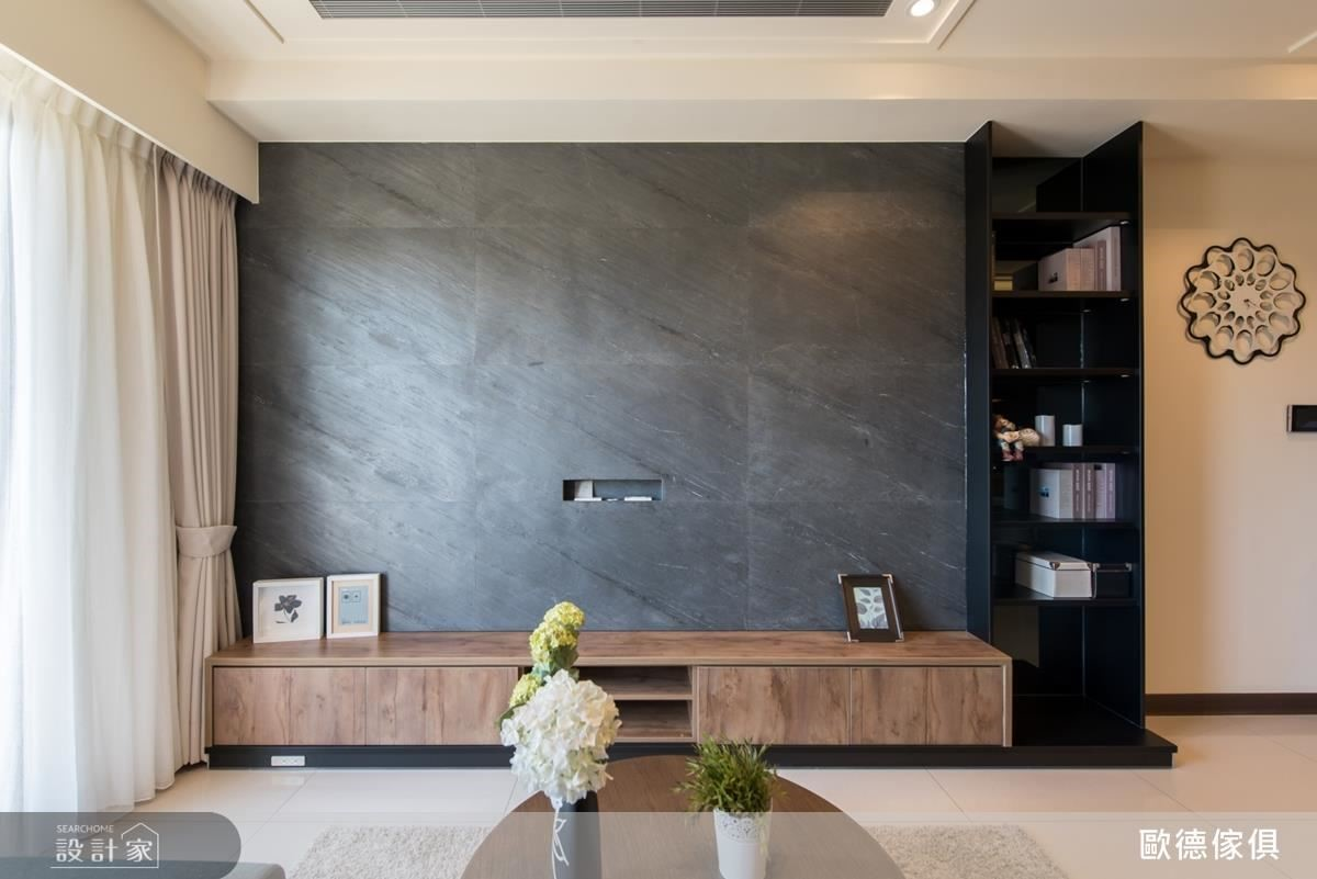 客廳電視牆面選用細緻灰色薄石板,延續空間調性,引入沉穩內斂感。
