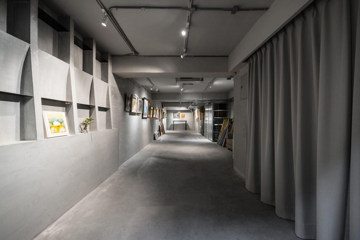 地下室畫廊以格狀展示櫃賦予空間機能,並考量光線投射於畫作的聚焦性,選用水泥鋪陳牆面避免反光的視覺問題。
