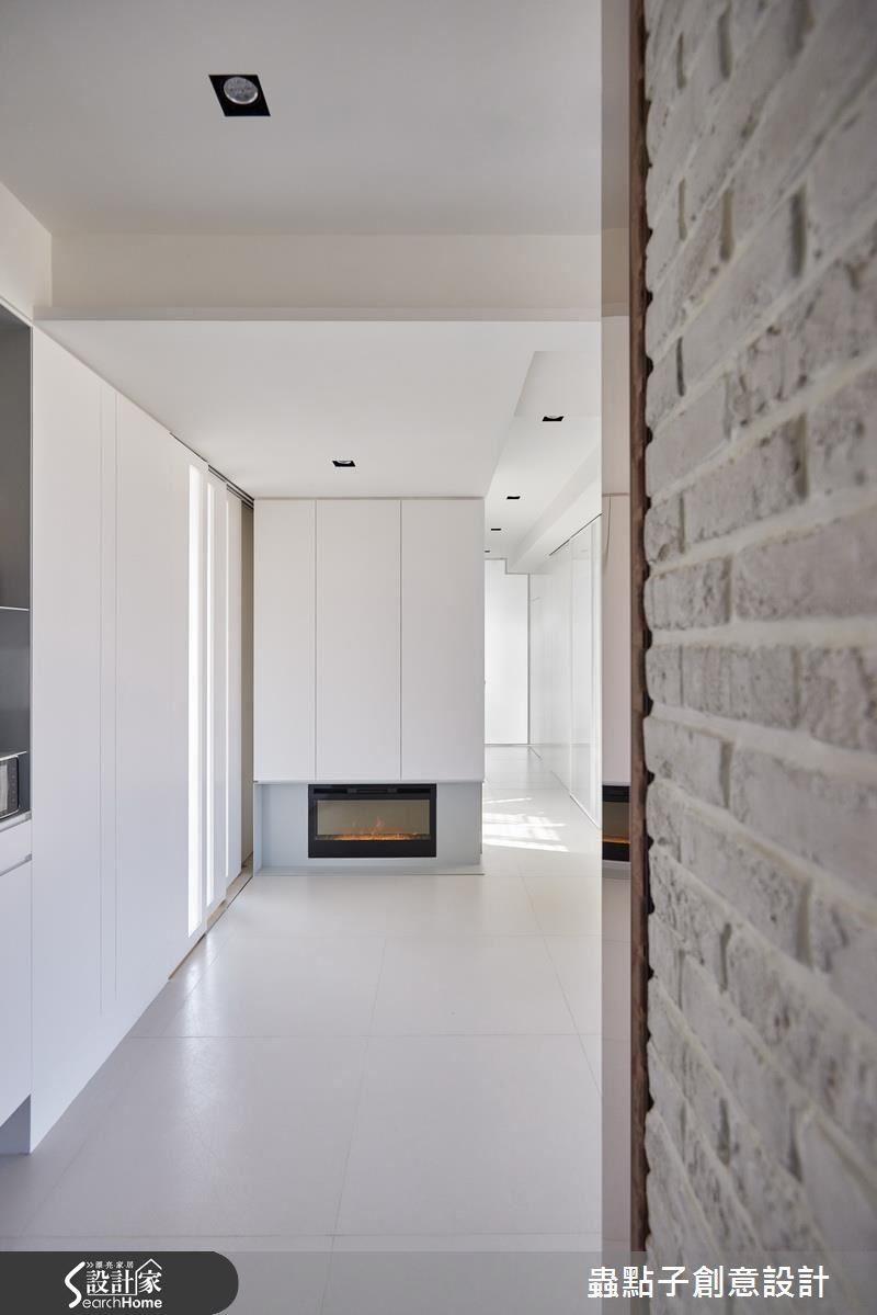 玄關牆面以文化石及鍍鈦鐵件鋪陳,前方則以壁爐作為端景,一旁搭以晶亮石英磚給予屋內純淨感受。