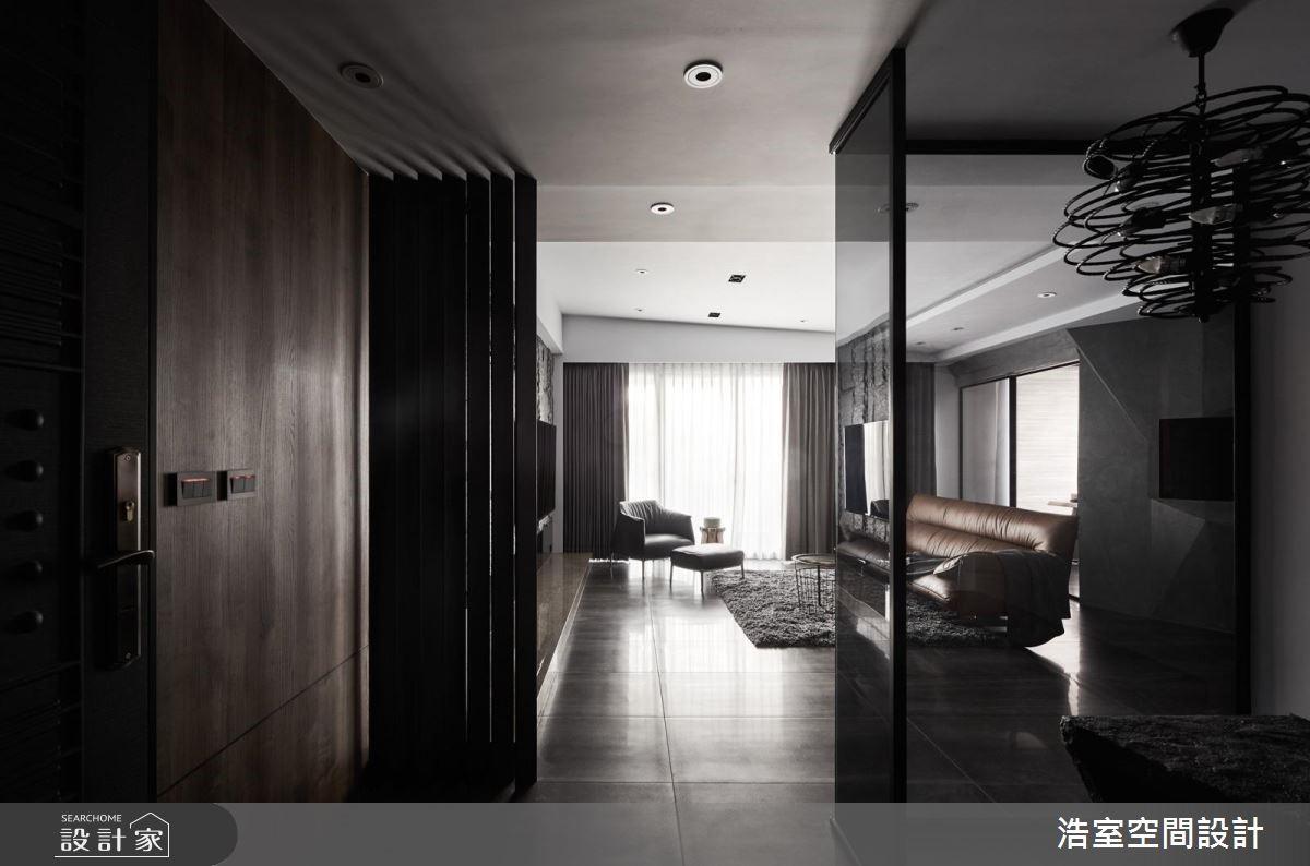 玄關以深木皮牆面鋪陳空間沉澱心情,運用格柵區隔出空間,並藉黑玻反照使空間感持續迴盪。