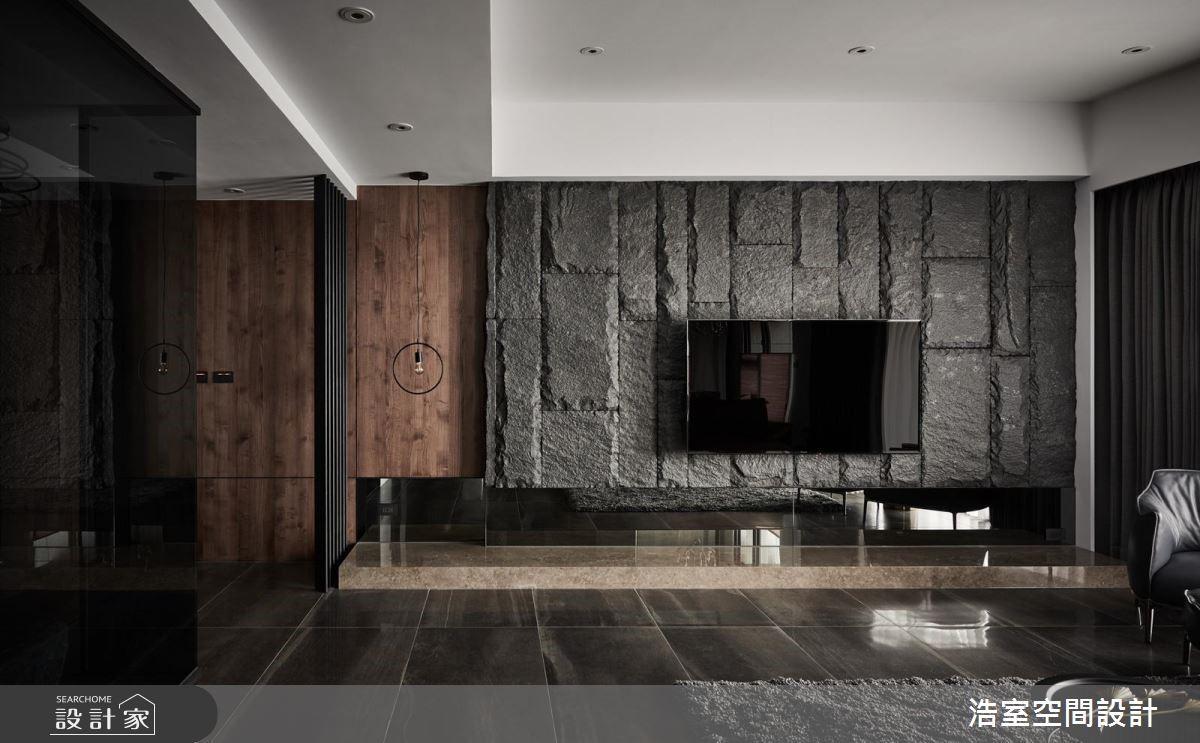 粗曠電視牆以石頭拼貼出磅礡立體感,於左側貼上木皮延續玄關牆面的溫潤沉靜,而牆面下方,則使用黑玻大幅提升空間質感。
