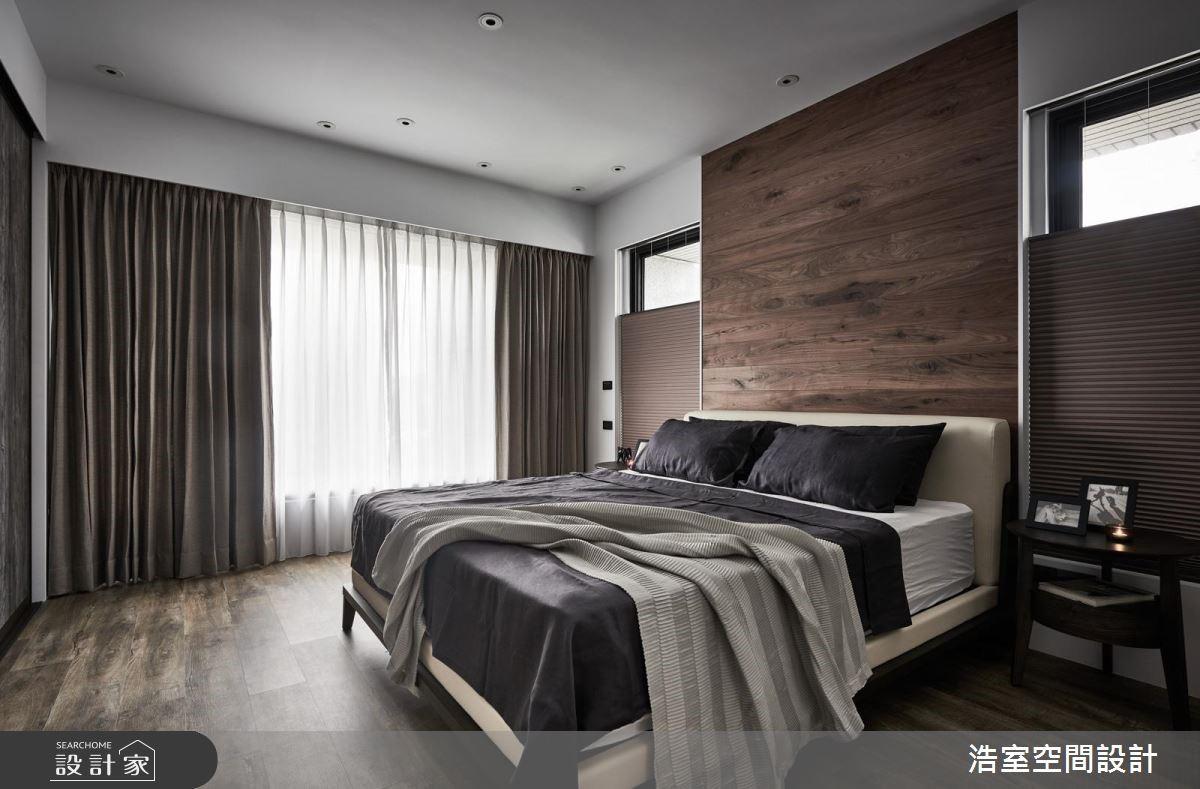 主臥床頭背牆使用深色木紋潤飾,為休憩空間傾注沉靜低調的大器質感。