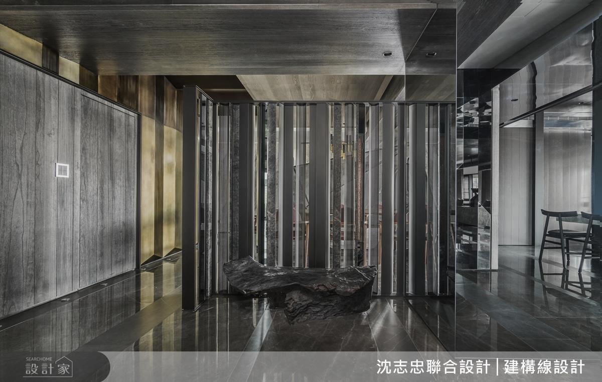玄關屏風運用鐵件、石材等,以不規則交錯排序,營造穿透性反射與虛實難辨的氛圍,兼具界定場域之作用。