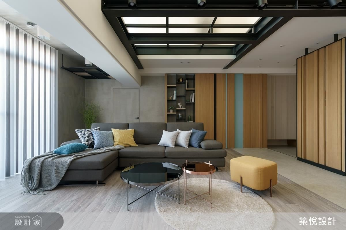 沙發背後的牆面包含臥室入口、開放式收納層架以及儲藏空間,利用粗黑框與藍綠色線條化解木色櫃面的單調,配合天花板的H型鋼,為輕工業的空間注入活潑元素。