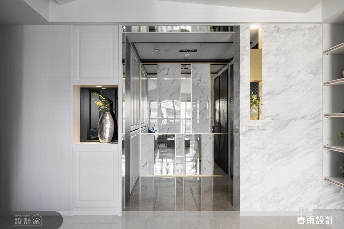 玄關牆面運用鈦金線條切割,營造簡約俐落的精緻感。