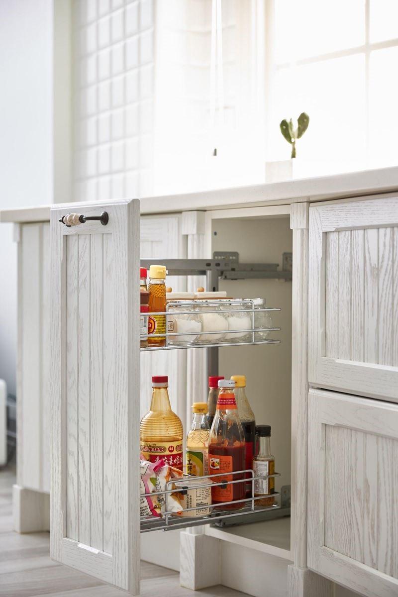 由於女屋主希望工作檯上維持乾淨,特別打造側拉籃地櫃來收納各式調味料,料理時可輕鬆拉開櫃體,輕鬆選取使用。