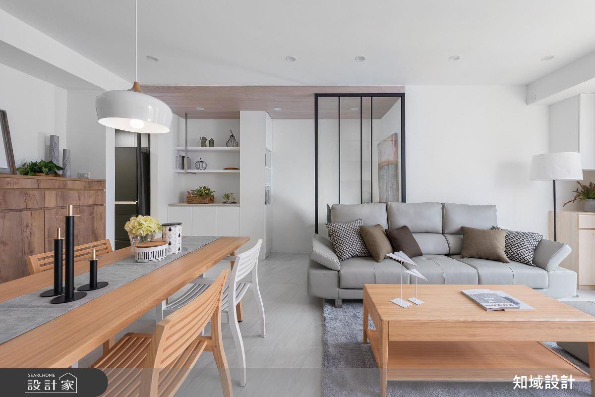簡單的玻璃鐵件屏風,區隔出客廳與玄關的空間,空間整體灰白黑的配色略微冷調,使用木質家具在空間裡注入了溫潤的氛圍。